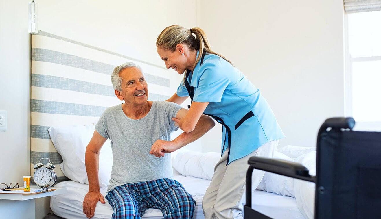 caregiver assisting senior man to stand