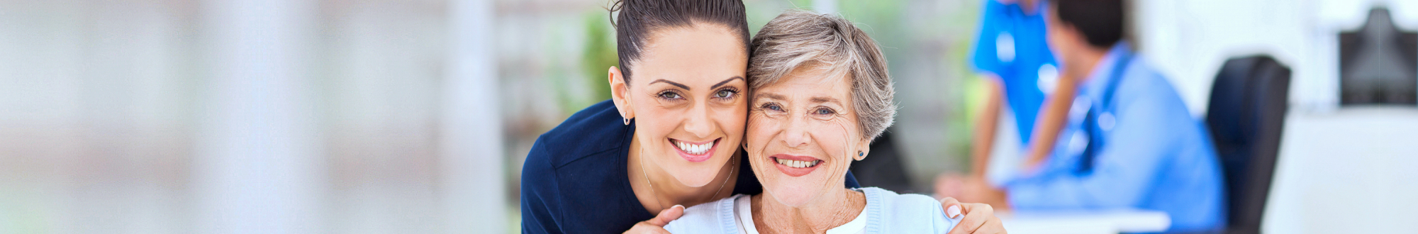 caregiver smiling while hugging senior woman