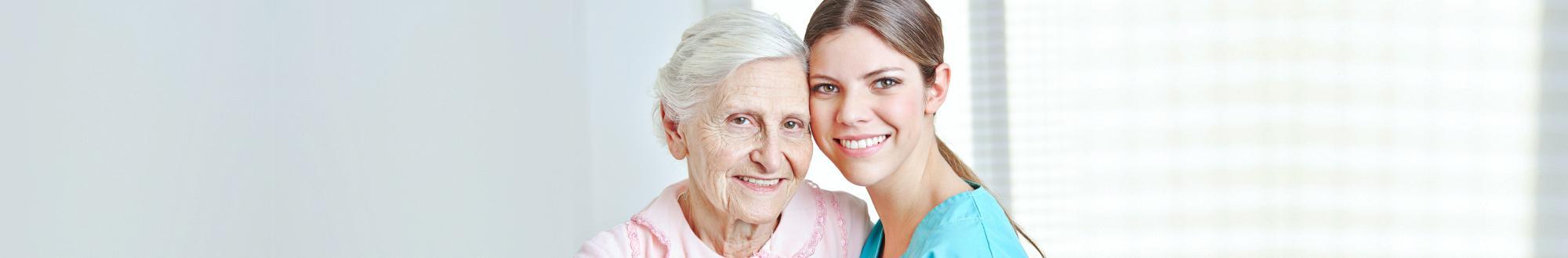 senior woman and female caregiver smiling